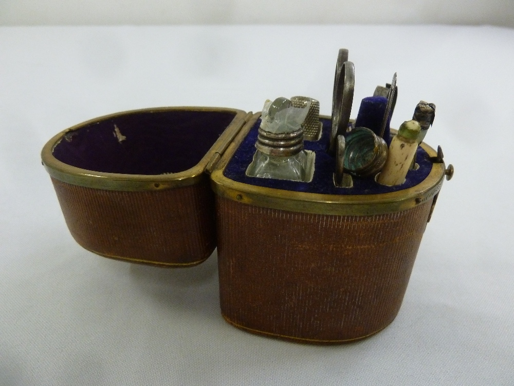 Lot 291 - An English leather cased travelling manicure set to include scissors, a scent bottle and a file, A/