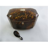 Lot 297 - An early 19th century tortoiseshell tea caddy of elongated octagonal form the hinged cover revealing