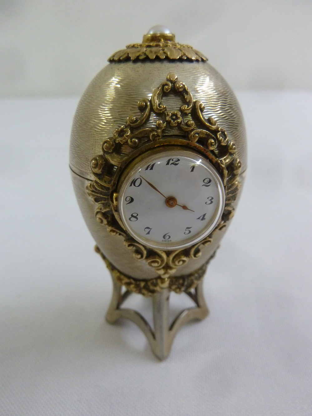 Lot 351 - An engine turned silver Easter Egg desk clock with silver gilt mounts on integrated stand and