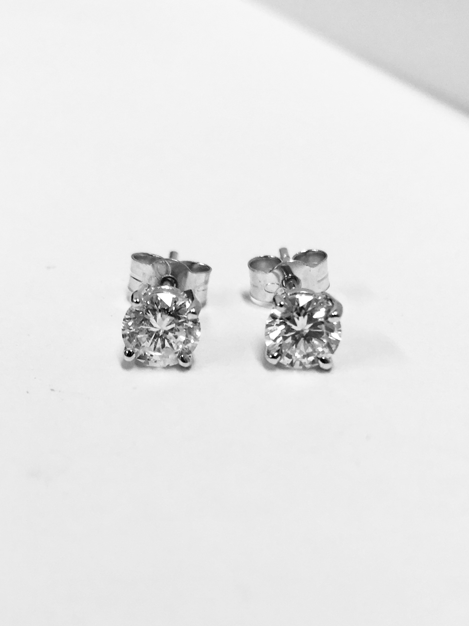 Lot 15 - 1.00ct Solitaire diamond stud earrings set with enhanced brilliant cut diamonds, SI3 clarity and H