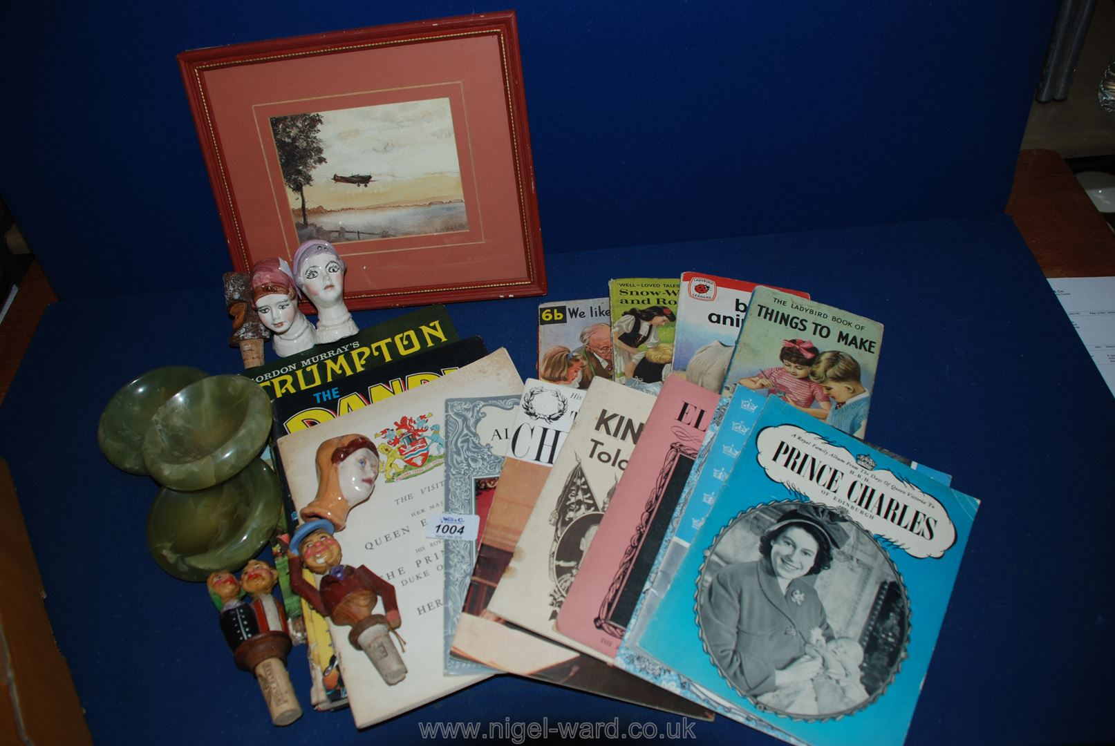 Lot 1004 - A box of Ladybird books, painting of Spitfire, carved bottle stoppers,