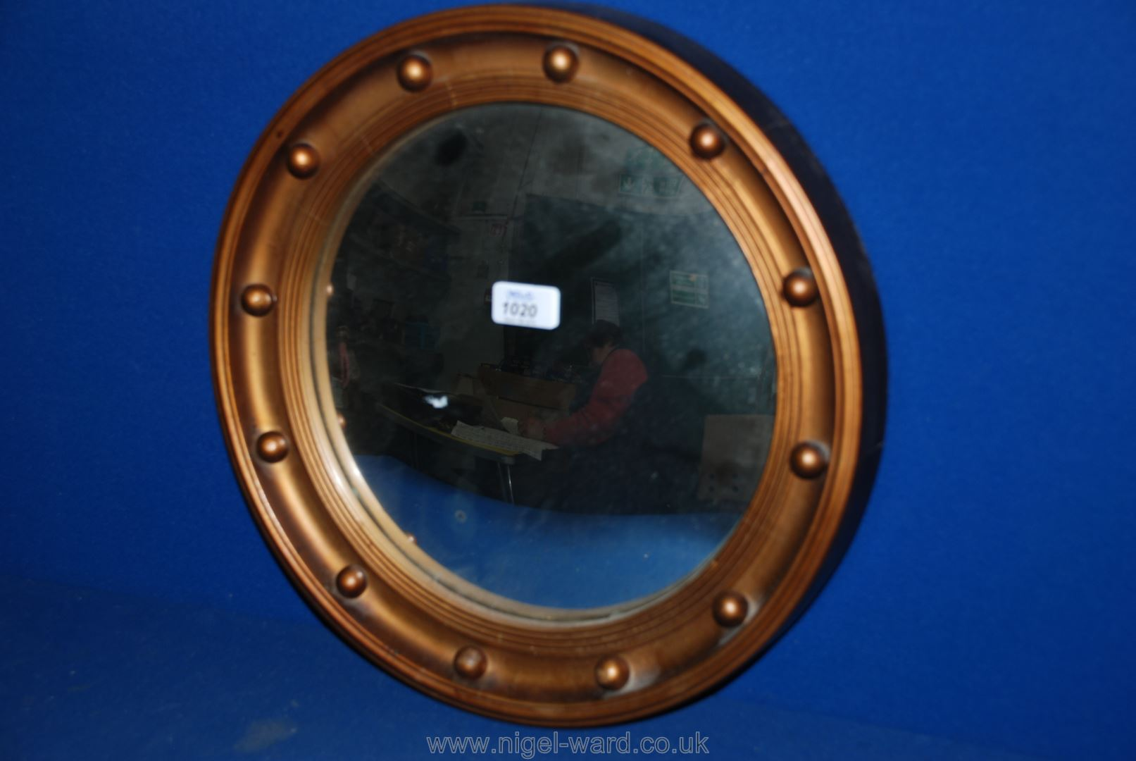 Lot 1020 - A circular convex wall mirror with a wooden framed with a gold- coloured rim.