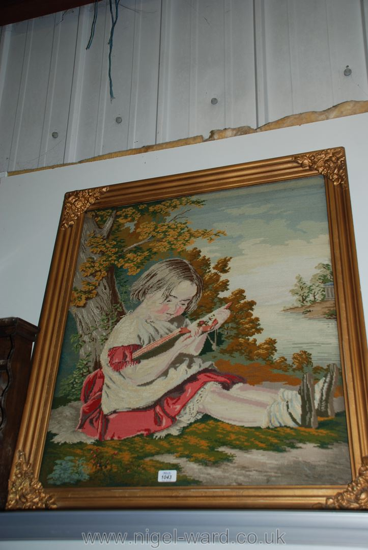 Lot 1043 - A Victorian Woolwork embroidery picture of a young girl reading under a tree,