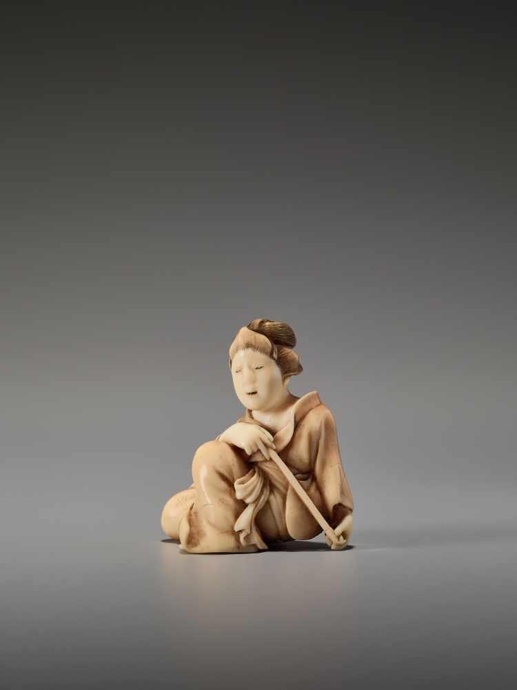 Los 59 - AN IVORY SHUNGA NETSUKE OF A BIJIN WITH PIPE BY KOHOSAIBy Kohosai, ivory shunga netsukeJapan, Osaka,