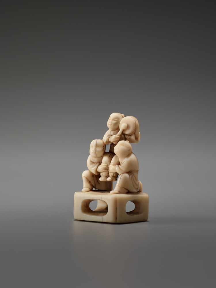Los 25 - AN IVORY NETSUKE OF THREE CHINESE BOYS AND A DRUMUnsigned, ivory netsukeJapan, late 18th to early