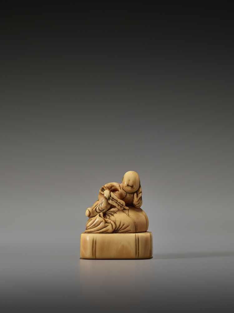 Los 22 - AN EARLY IVORY NETSUKE OF A CHINESE BOY ON HOTEI'S SACKUnsigned, ivory netsukeJapan, 18th century,