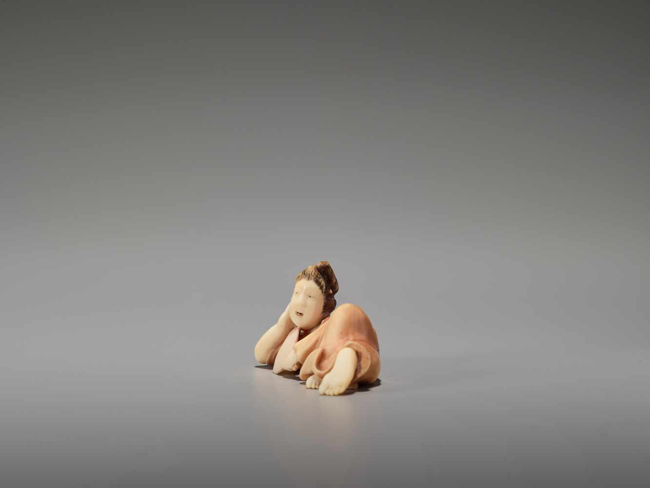 Los 57 - AN IVORY SHUNGA NETSUKE OF A RECLINING BIJIN WITH FAN BY KOHOSAIBy Kohosai, ivory shunga