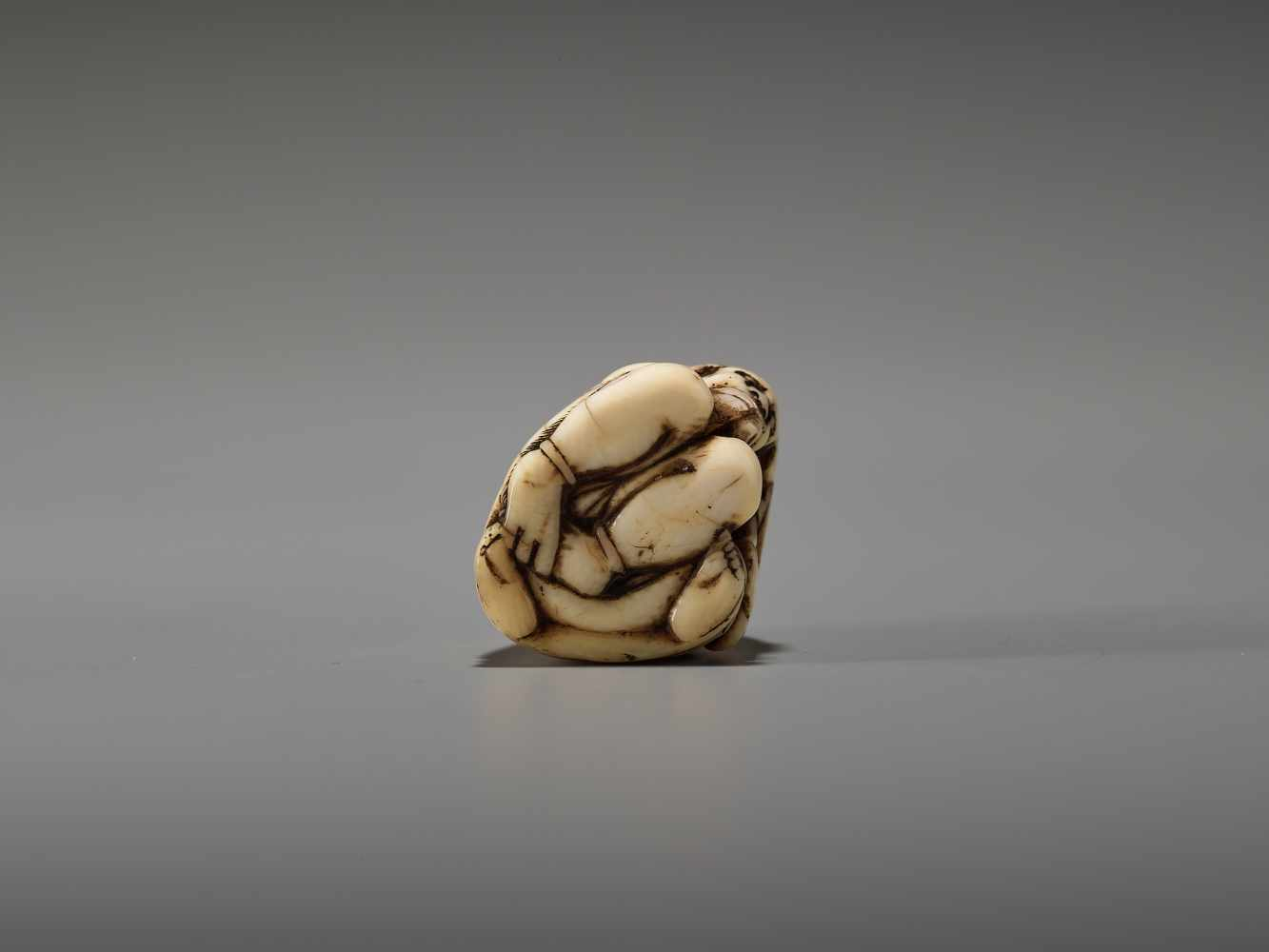 Los 41 - AN IVORY NETSUKE OF A MONK AND REPENTANT ONIUnsigned, Tomochika school, ivory netsukeJapan, mid to