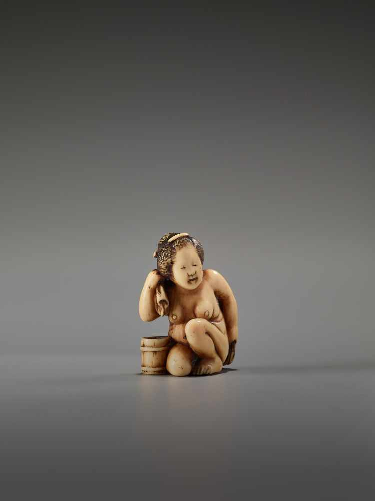 Los 51 - AN IVORY SHUNGA NETSUKE OF A NUDE WOMAN WASHING HERSELF BY THE TOMOCHIKA SCHOOLBy Tomochika, ivory