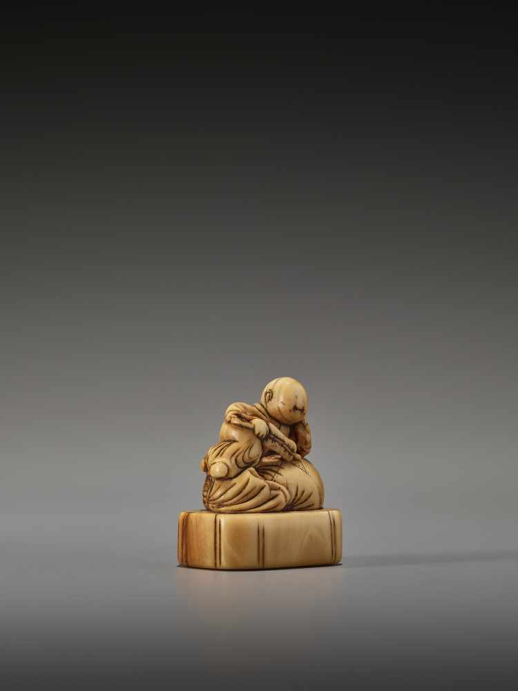Lot 22 - AN EARLY IVORY NETSUKE OF A CHINESE BOY ON HOTEI'S SACKUnsigned, ivory netsukeJapan, 18th century,