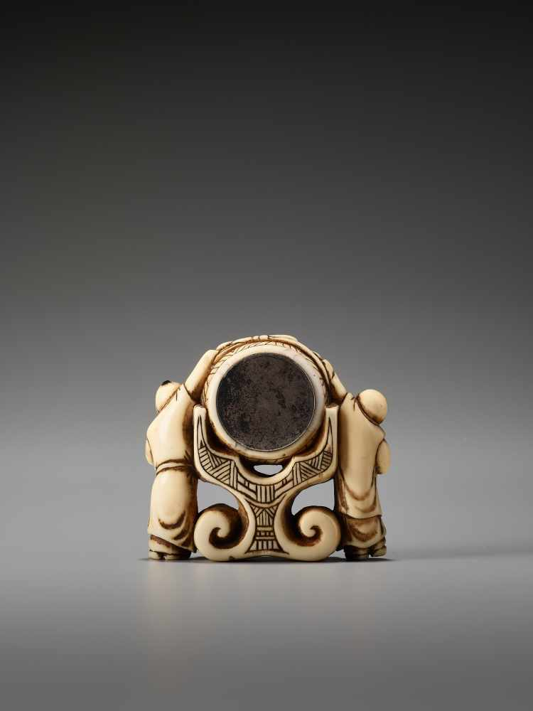 Los 26 - A RARE AND UNUSUAL IVORY NETSUKE OF TWO CHINESE BOYS AT A PALACE GONGUnsigned, ivory netsuke with