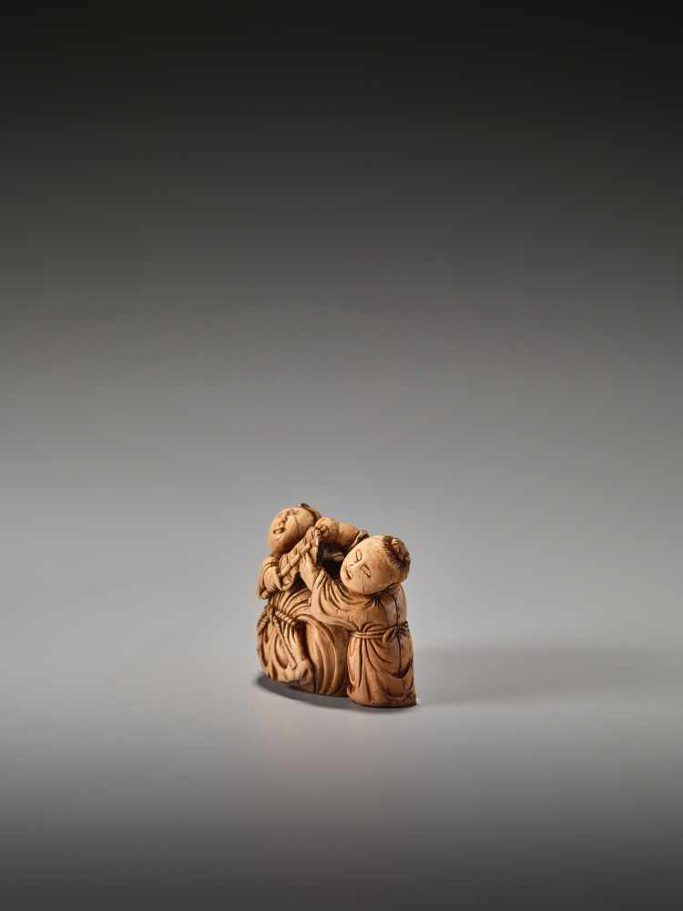 Los 23 - A VERY RARE 17TH CENTURY IVORY NETSUKE OF TWO CHINESE BOYS WITH HOTEI'S SACKUnsigned, ivory