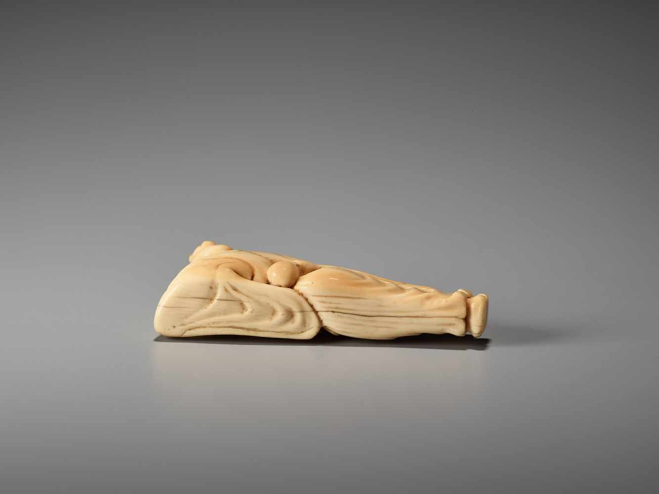 Los 9 - AN IVORY NETSUKE OF A RECLINING CHINESE IMMORTAL WITH A FANUnsigned, ivory netsukeJapan, late 18th
