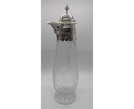 A 19th century silver plated wine carafe, the spout in the form of a bearded mans head, vacant cartouche, etched glass body,