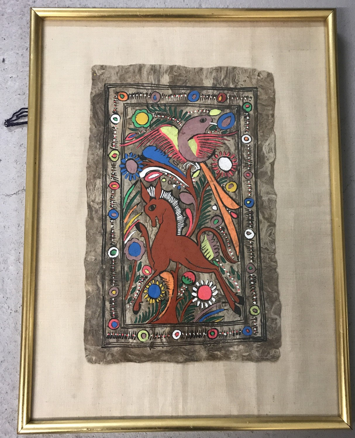 Lot 155 - An ethnic painted natural fibre panel, framed and glazed.