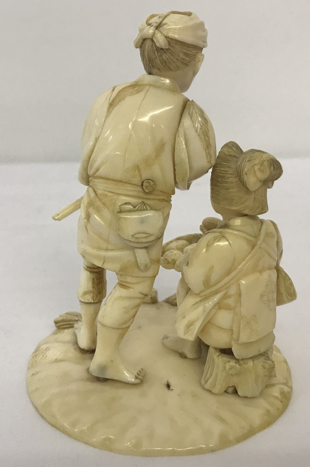 Lot 133 - An antique carved ivory figure of an oriental lady and gentleman.