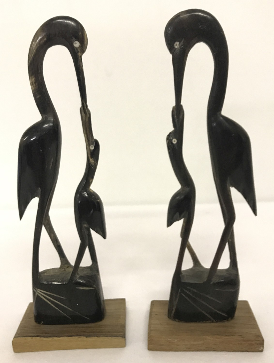 A pair of Indian carved horn figurines of stalks on wooden plinths.