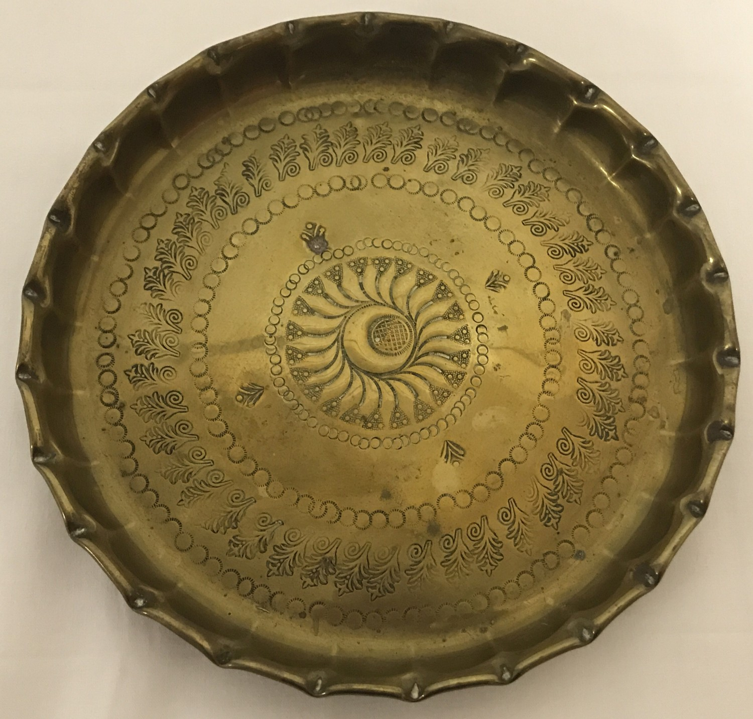 A brass circular dish with hammered Persian decoration to interior and shaped rim.