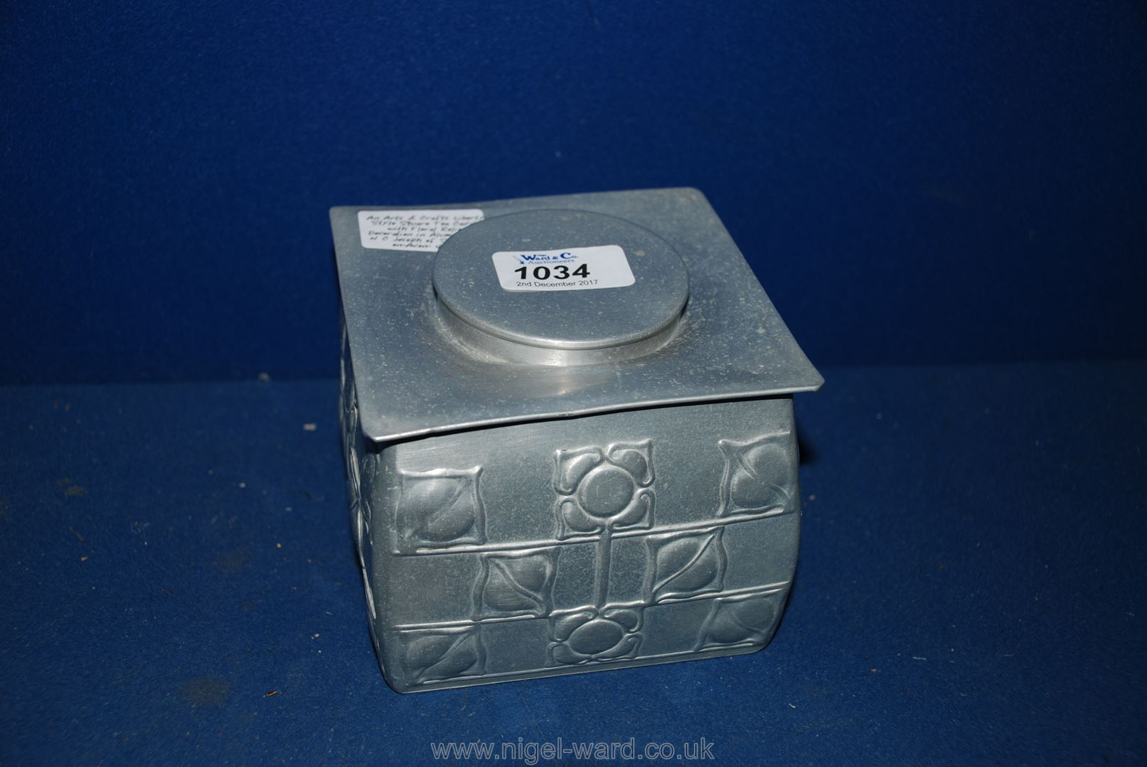 Lot 1034 - An Arts & Crafts Liberty Style Square Tea Caddy with Floral Relief Decoration in Aluminium by N C