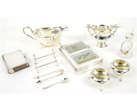 Group of silver items including a large silver sauce boat engraved with a crest, two open salts, a dragon-handled sugar bowl,