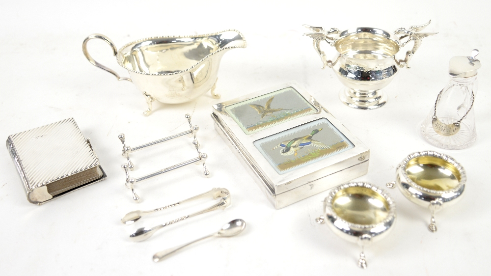 Group of silver items including a large silver sauce boat engraved with a crest, two open salts, a