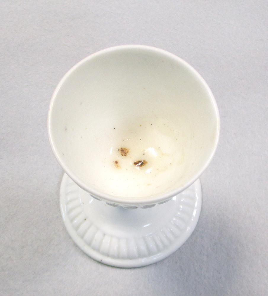 Lot 20 - A rare Saint-Cloud blanc de chine egg cup, circa 1730-50, the bowl raised on a knopped stem and