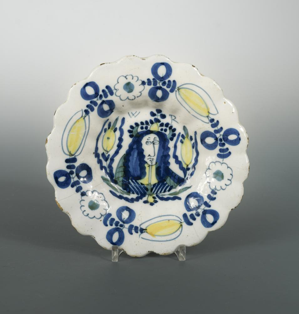 Lot 43 - A late 17th Century Delft lobed plate, decorated in blue and yellow with a portrait of King