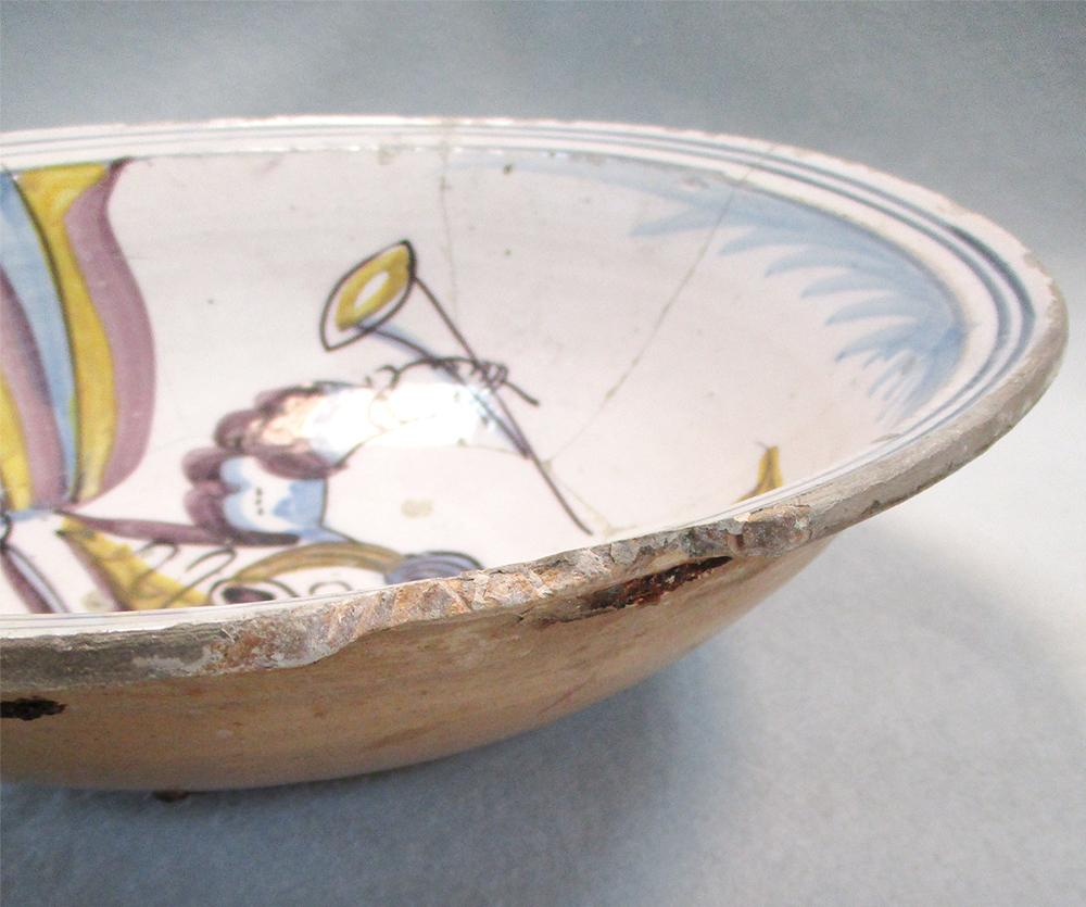Lot 44 - An 18th century Delft polychrome bowl, decorated with the figure of a woman holding a trumpet, in