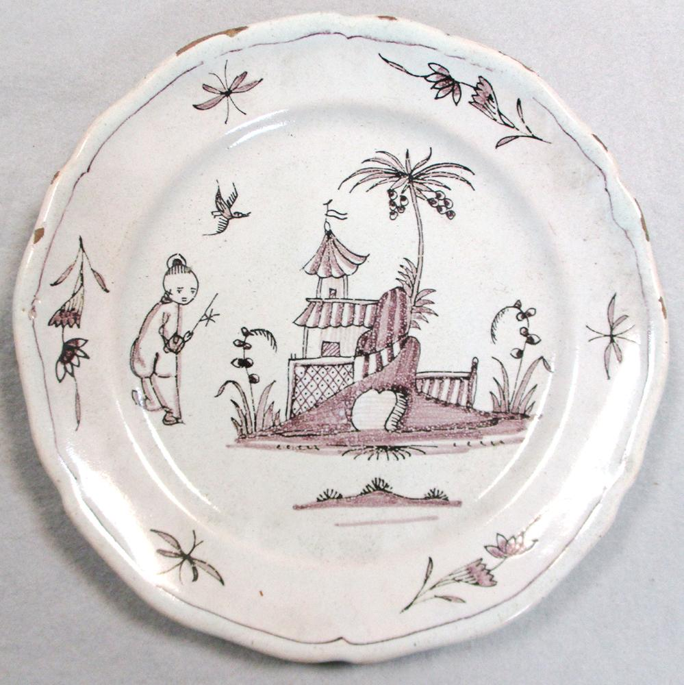 Lot 45 - An 18th century faience plate, decorated in manganese with a house, 29cm diameter, another decorated