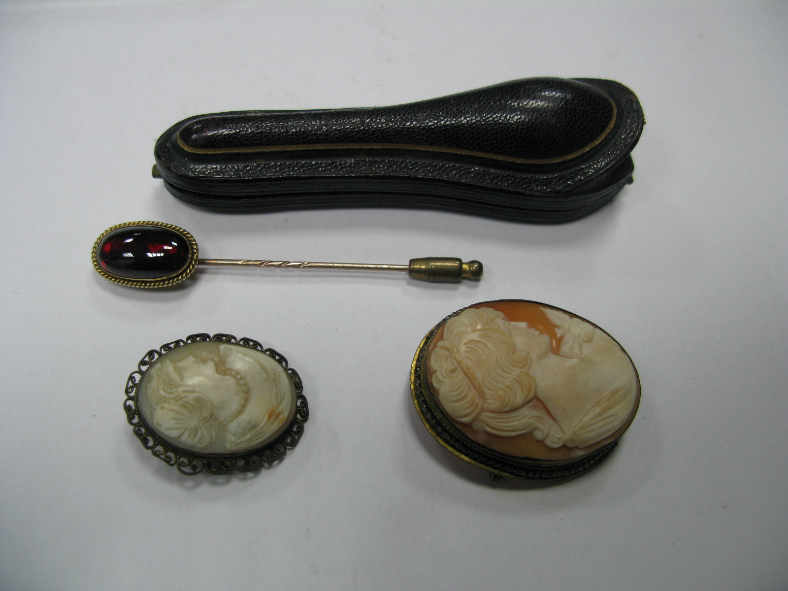 Lot 1388 - A XIX Century Stick Pin, the elongated oval cabochon collet set, in a case; together with two oval