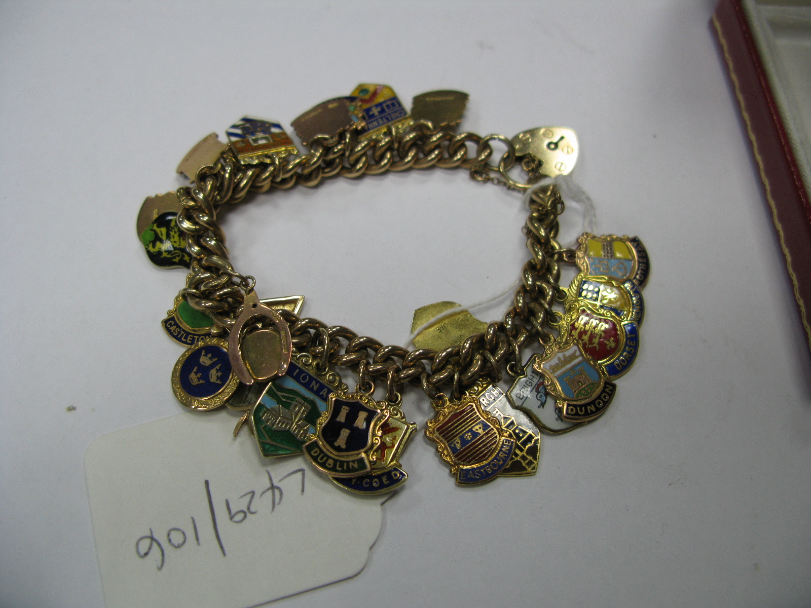 Lot 1387 - A 9ct Gold Curb Link Charm Bracelet, to 9ct gold heart shape padlock clasp, suspending numerous