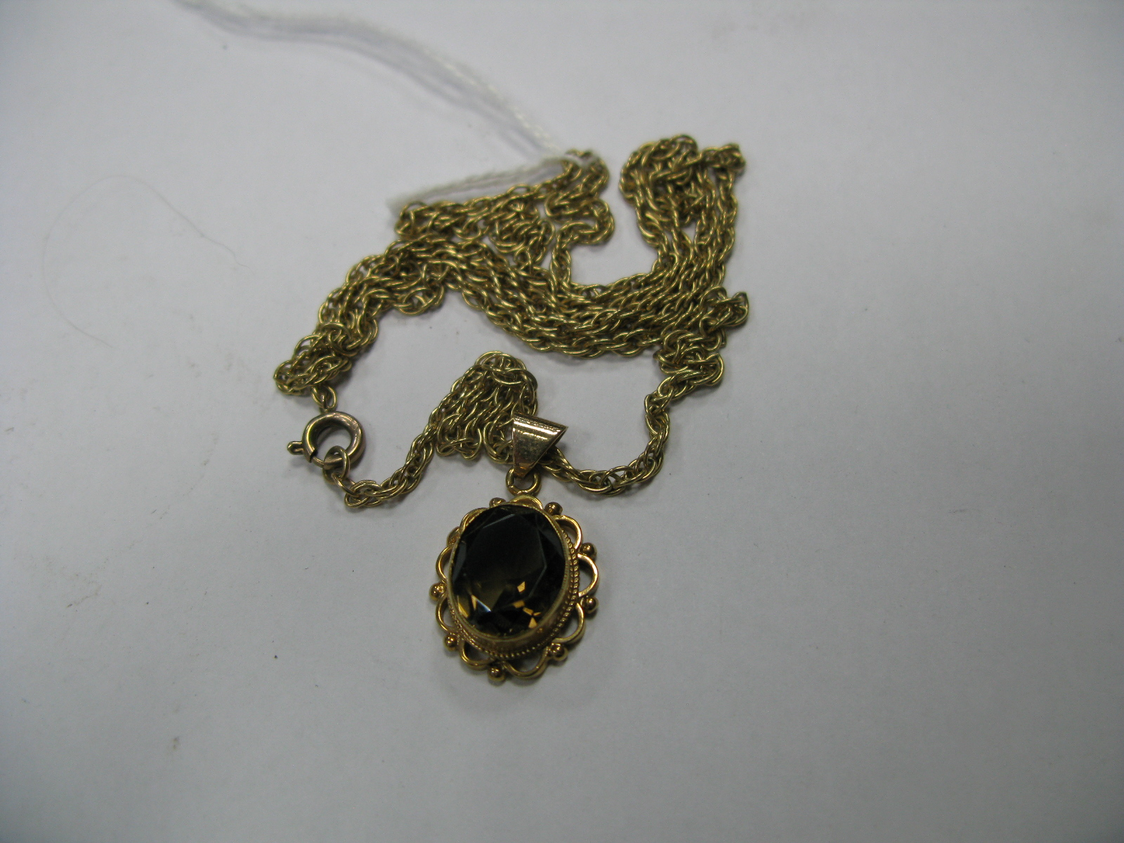 Lot 1400 - A 9ct Gold Single Stone Pendant, collet set, on a chain.