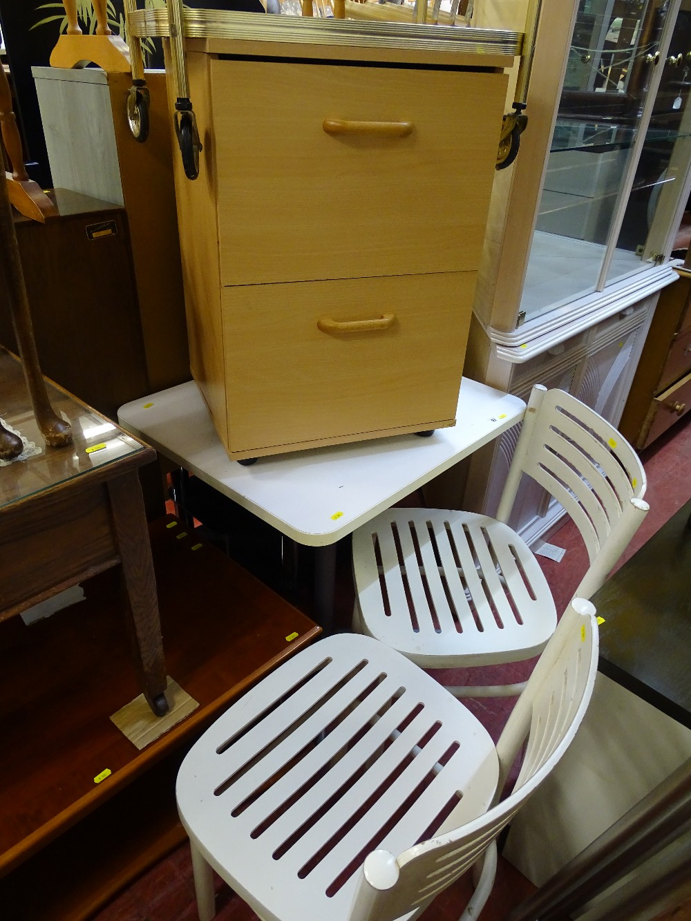 Lot 32 - Neat melamine kitchen table and two chairs (Ikea), a light wood melamine file cabinet and a brass