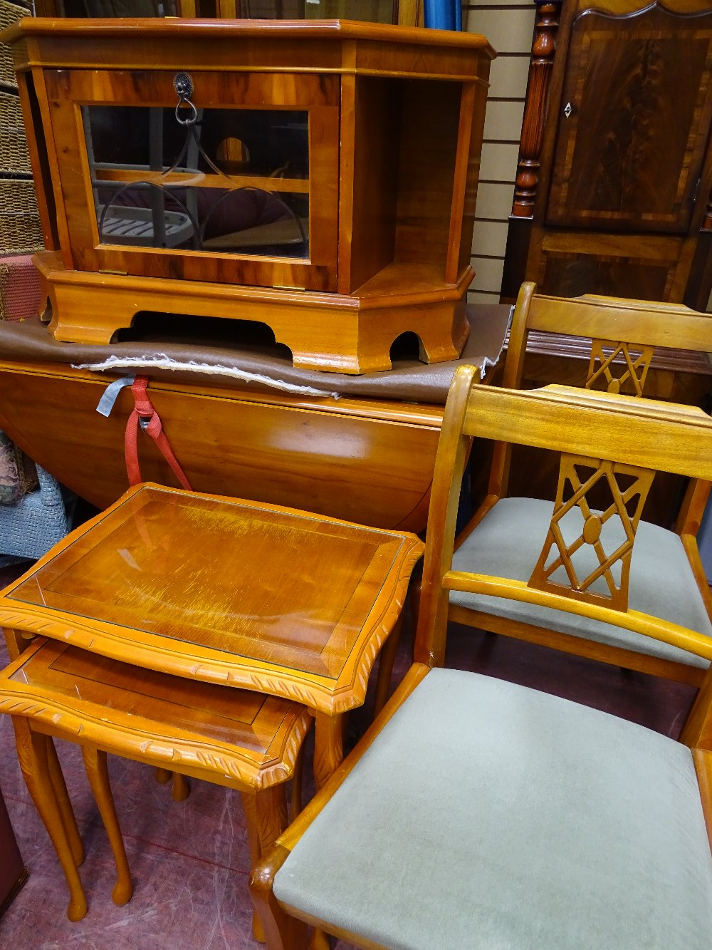 Lot 30 - Yew wood twin flap dining table and two chairs, a similar entertainment cabinet and a set of three