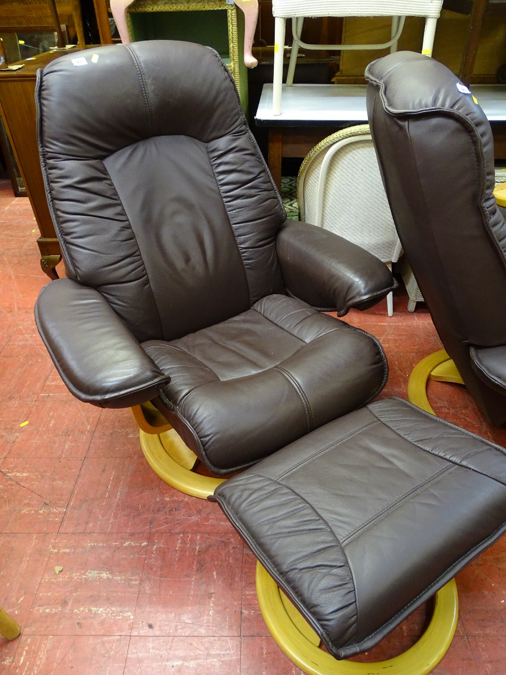 Lot 82 - Ultra modern brown leather effect swivel easy chair and matching footstool