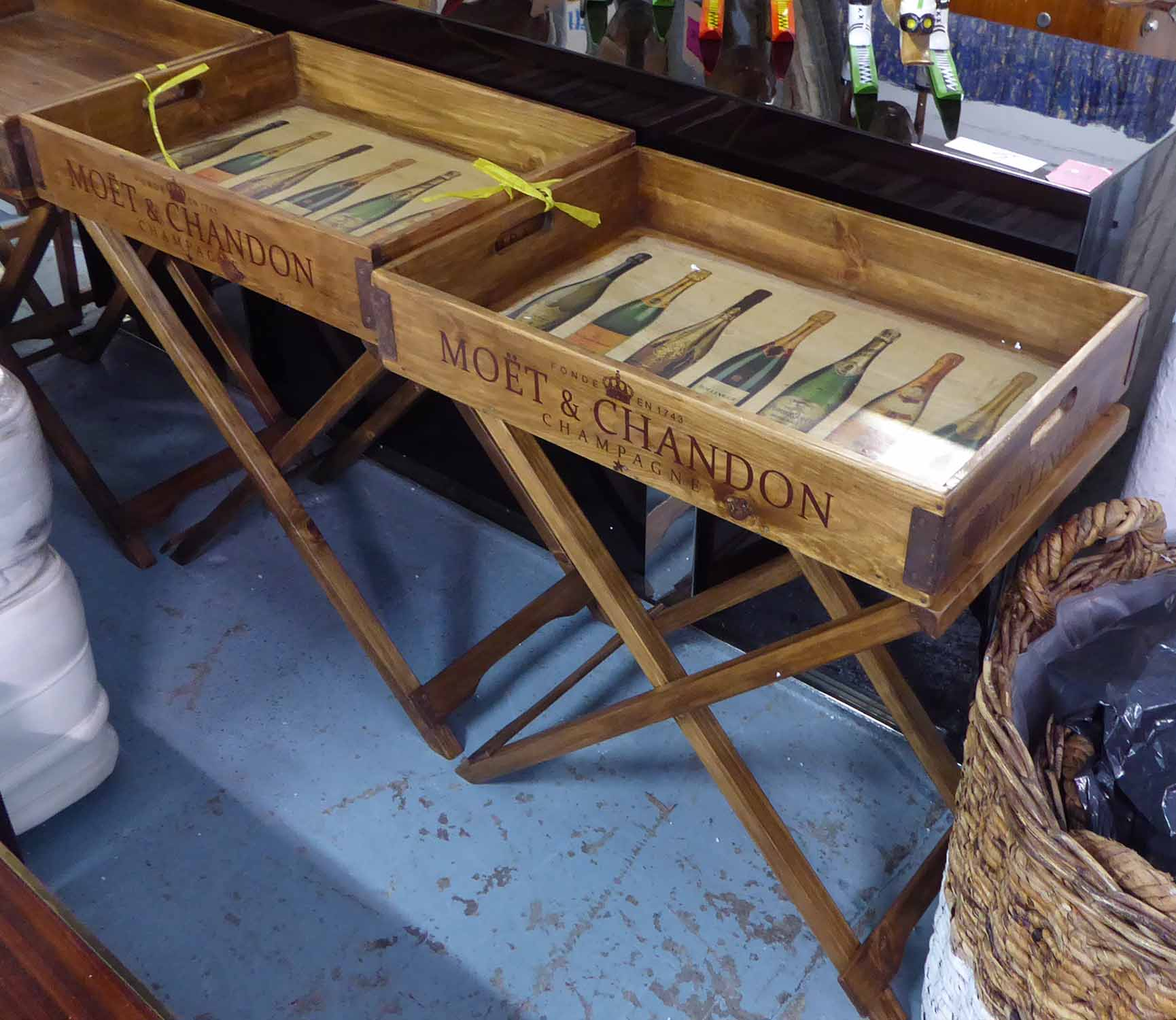 DRINKS TRAYS, a pair, on stands, stamped with various champagne houses, 77cm H x 65cm W x 45cm D.