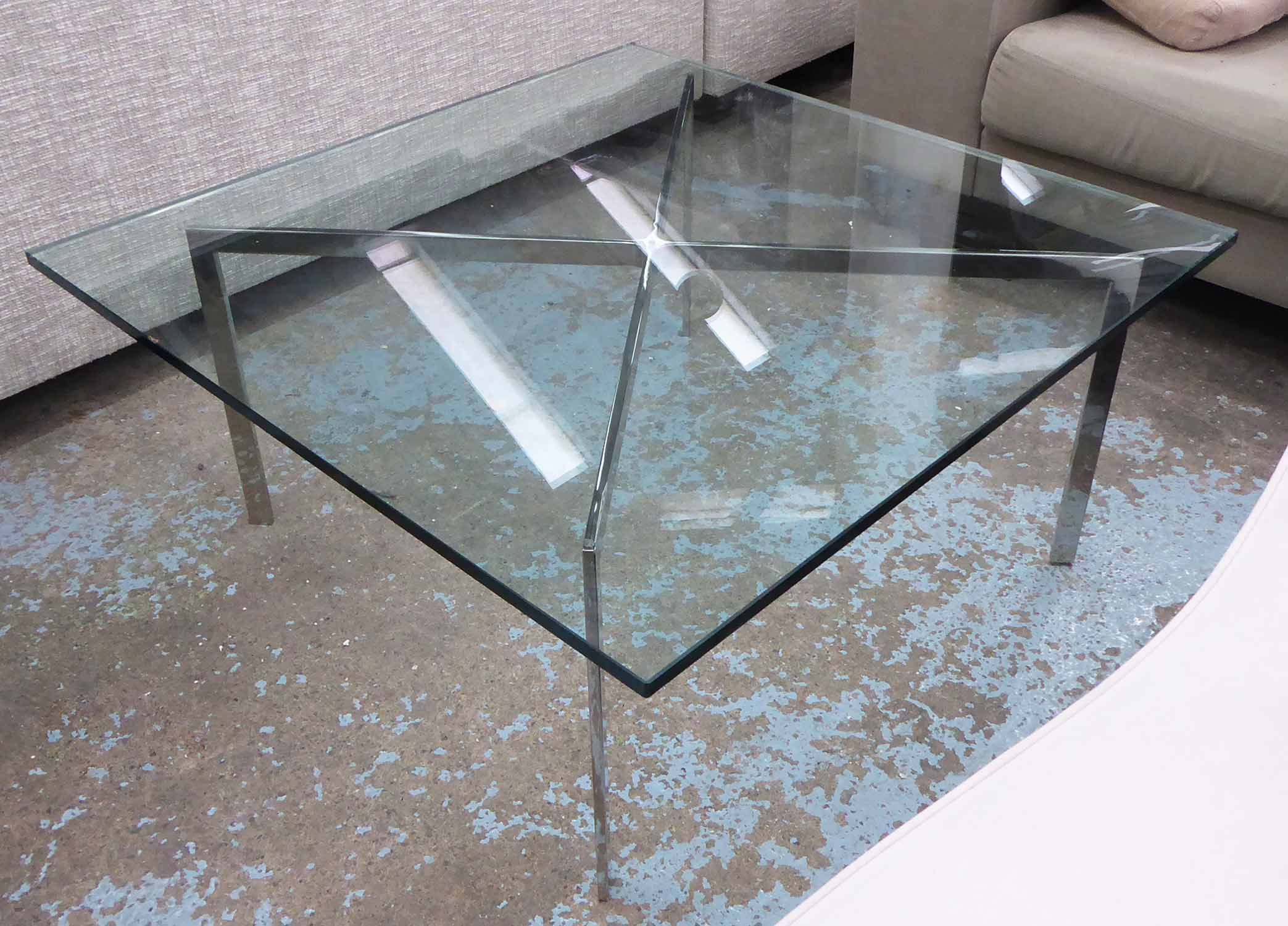 LOW TABLE, Barcelona style, the glass top on a polished metal base, 100cm W x 100cm D x 47cm H.