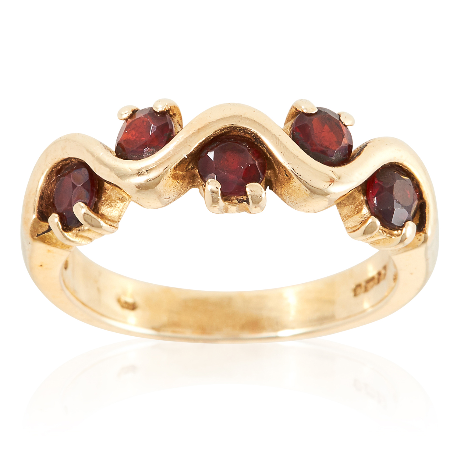 A GARNET DRESS RING in yellow gold, set with five round cut garnets in undulating form, British