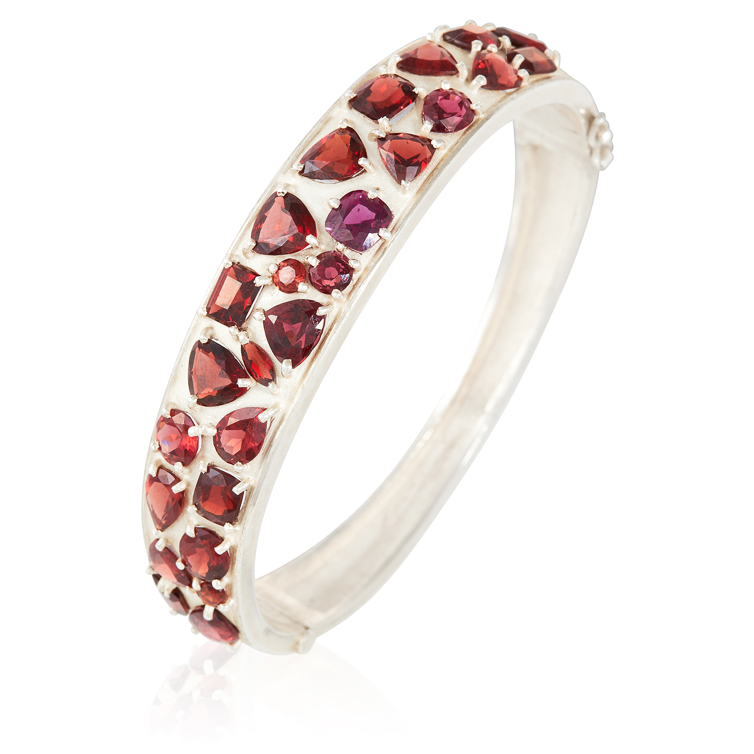 A GARNET BANGLE in sterling silver, set with round, pear, cushion and emerald cut garnets. 6cm inner