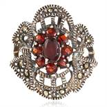 A MARCASITE AND RED GEMSTONE DRESS RING in sterling silver, set with oval and round cut red