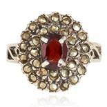 A MARCASITE AND RED GEMSTONE DRESS RING in sterling silver, set with an oval cut red gemstone in a