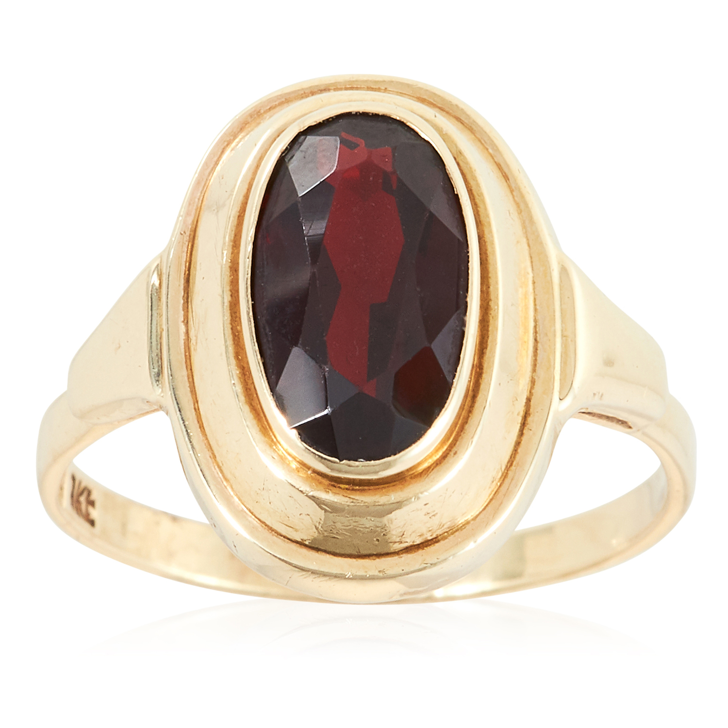 A GARNET DRESS RING in yellow gold, set with an oval cut garnet, stamped 9K, size O / 7, 2.7g.