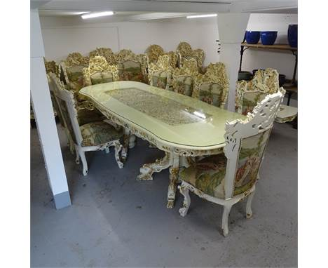 A bespoke made dining room suite, comprising a large serpentine-shape table, with an inset carved and pierced central panel,