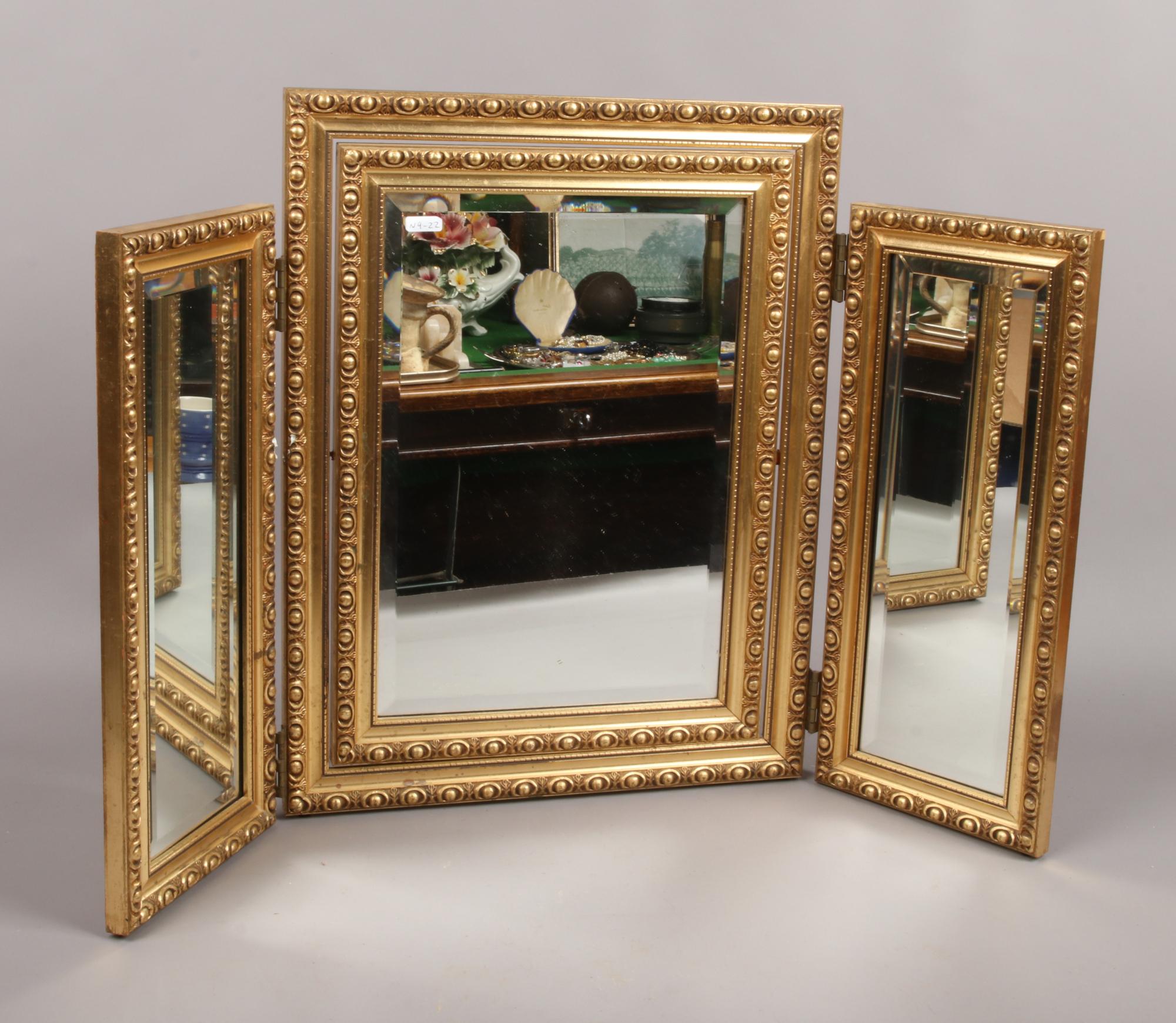 Lot 10 - A gilt frame bevel edge triple dressing table mirror.