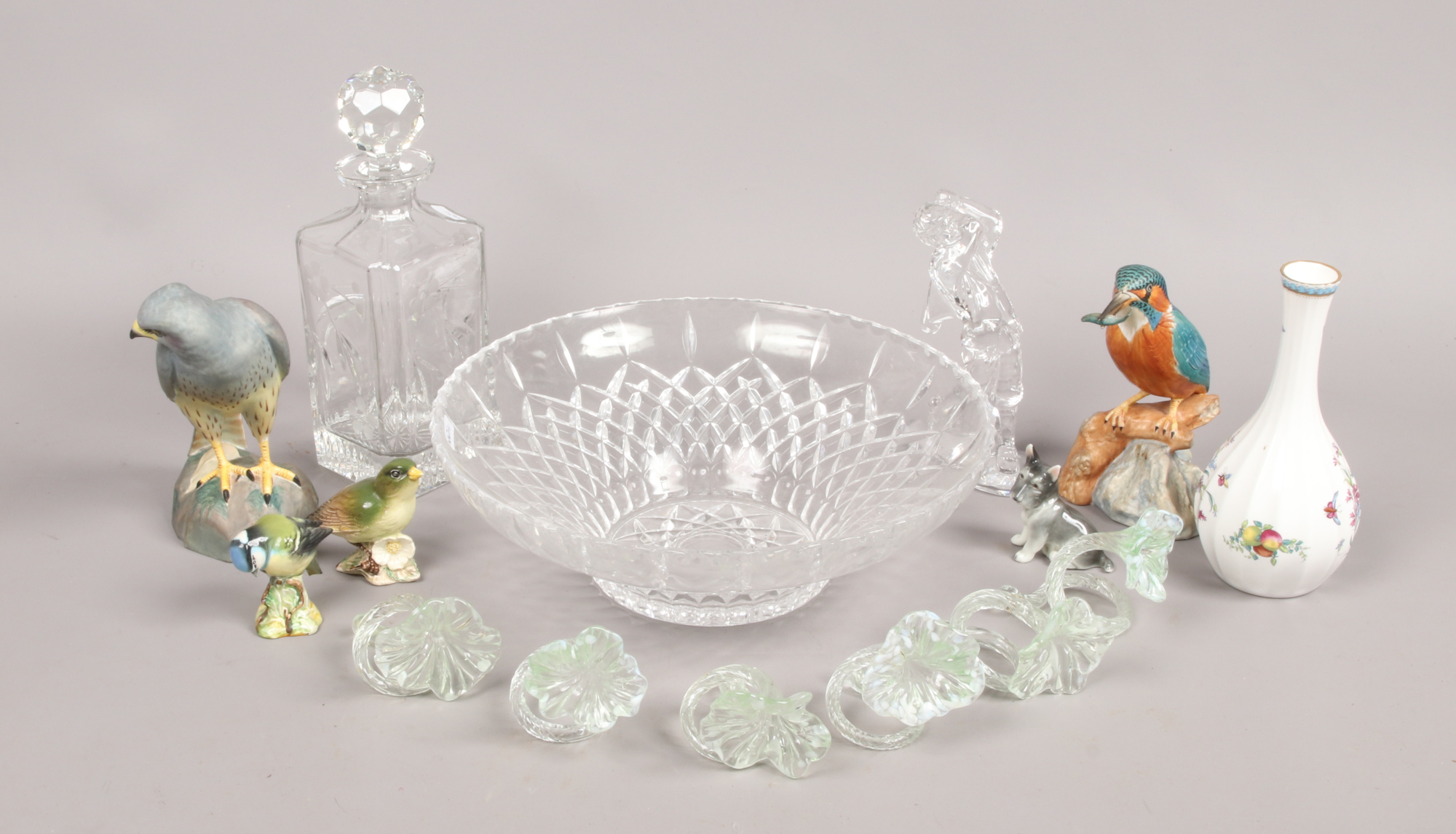 Lot 6 - A cut and etched glass decanter, fruit bowl, floral napkin rings, ornamental clear glass golfer,