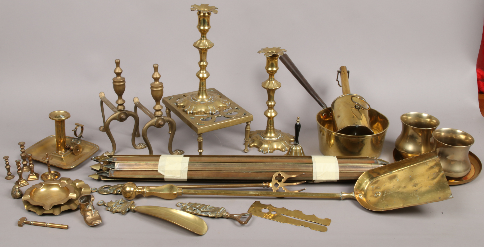 Lot 12 - A collection of brassware to include Spitjack, candlesticks, firedogs, chamber stick and a bundle of
