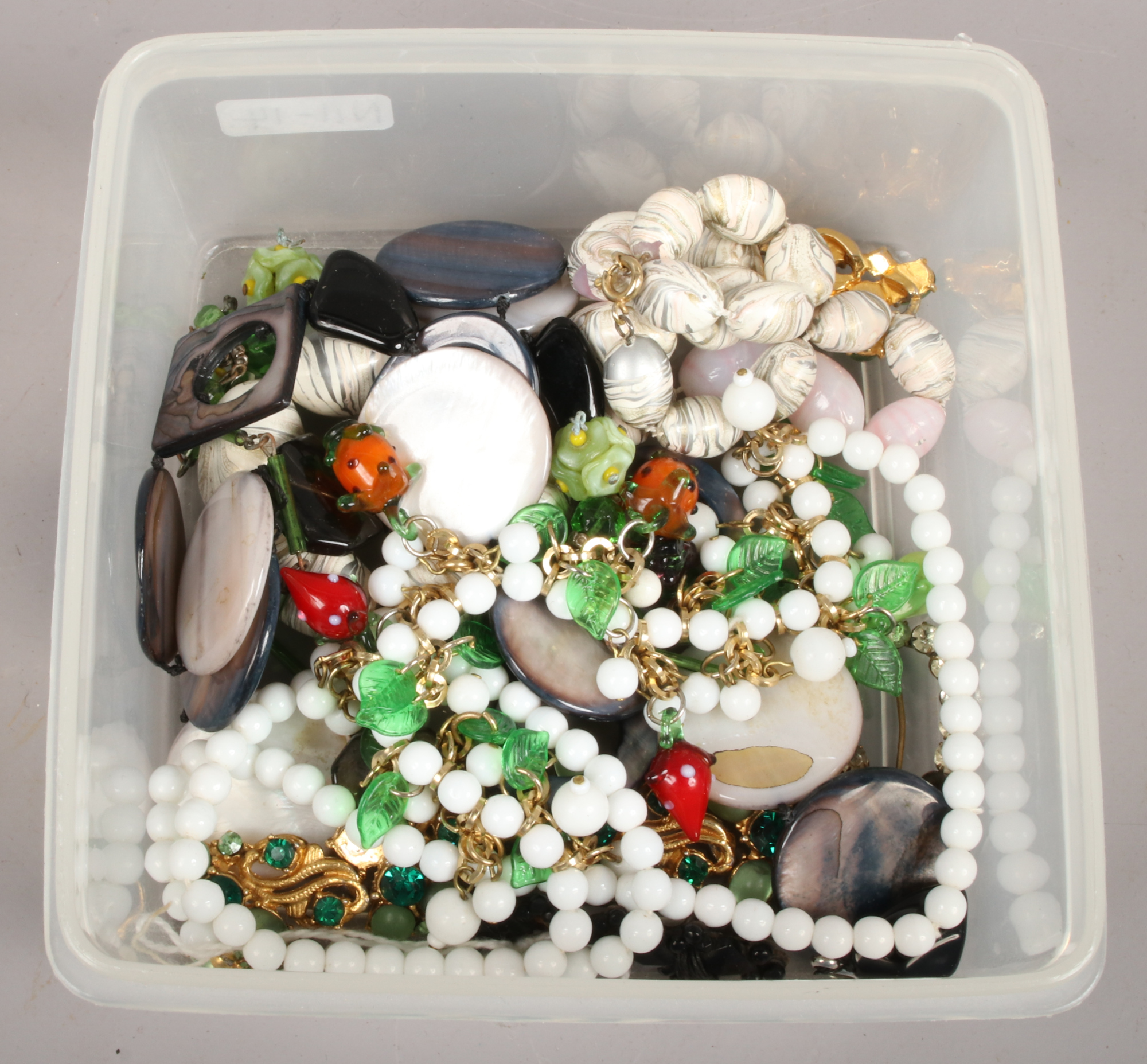 Lot 53 - A box of vintage costume jewellery including a novelty glass fruit necklace, brooches etc.