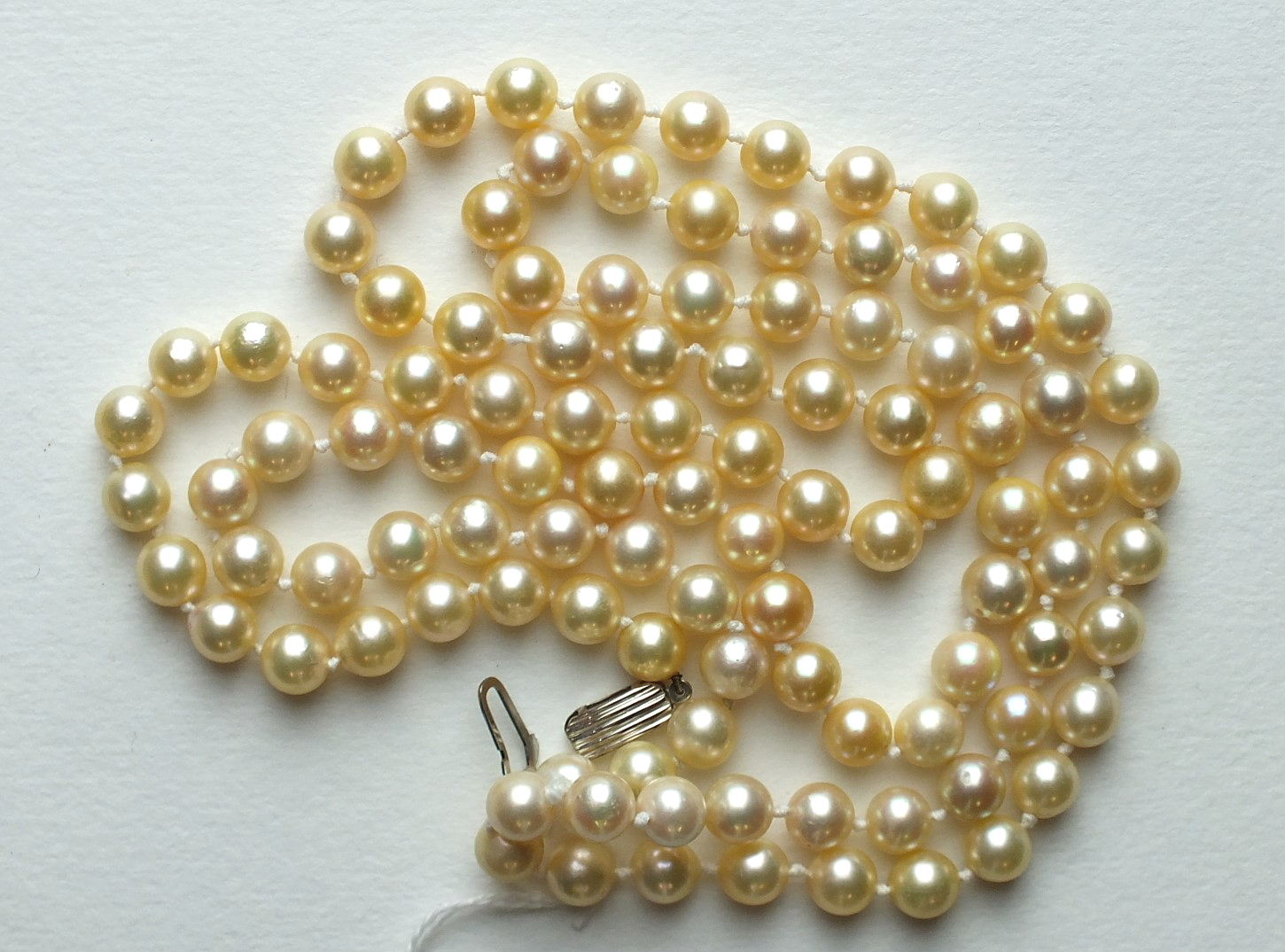 A long string of uniformly-sized cultured pearls, 7.5mm diameter, 100cm long, with 9ct white gold