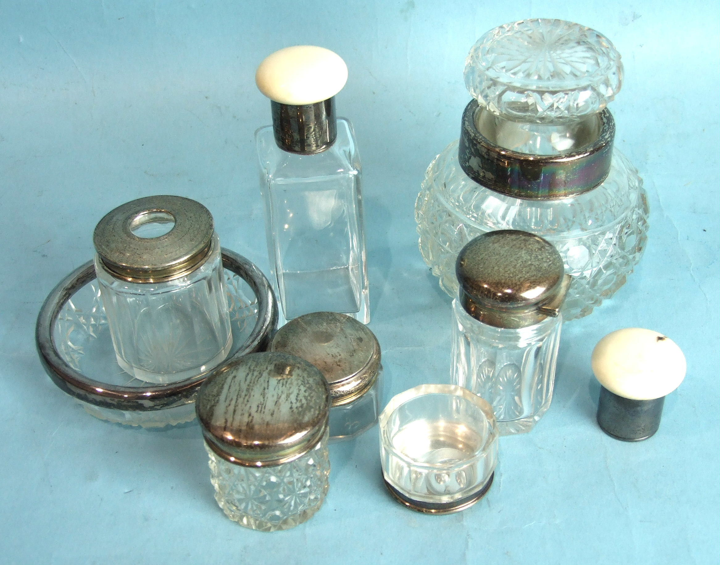 Lot 377 - A cut-glass dressing table bottle with silver collar mount and other silver-mounted bottles.