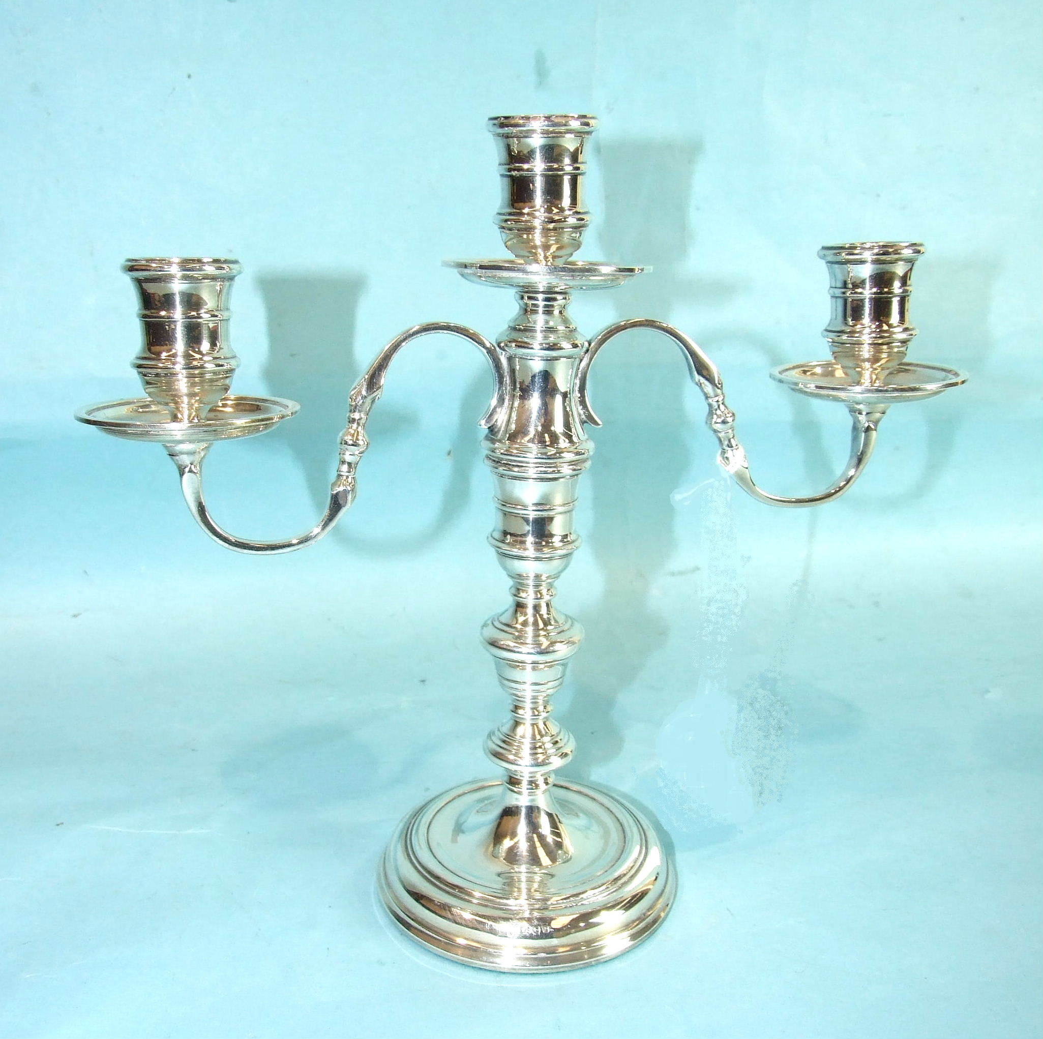 Lot 358 - A modern loaded table candelabrum with three sconces and turned stem, 25cm high, London 1972.